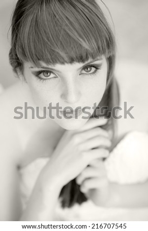 Black and white portrait of a beautiful, caucasian, young, long haired woman wearing a white dress, looking happy