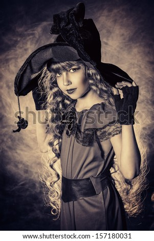 Black-and-white portrait of a beautiful little girl in a costume of witch. Vintage style. - stock photo