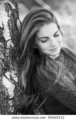 Black and white portrait of a beautiful woman against a tree. - stock photo