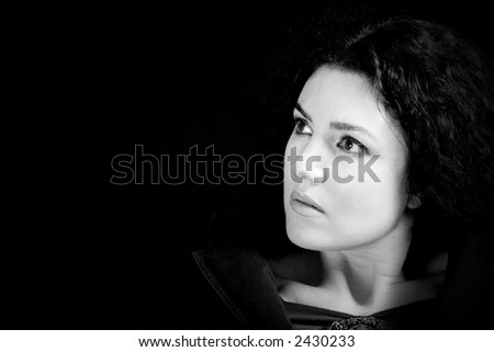Black and White portrait of a beautiful woman with mysterious look. Copy space. - stock photo