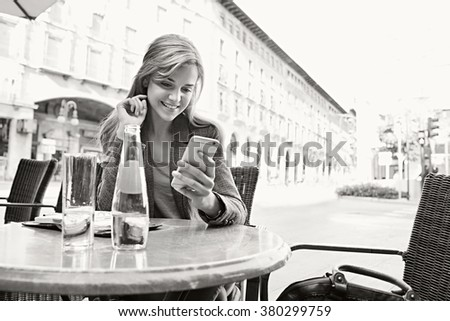 Black and white portrait of a beautiful young business woman at a coffee shop terrace with a laptop computer, using a smart phone. Professional smiling woman using technology, outdoors lifestyle. - stock photo