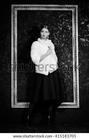 Black-and-white portrait of a beautiful young woman wearing mink fur jacket. Jewellery. Beauty, fashion. Studio shot.  - stock photo