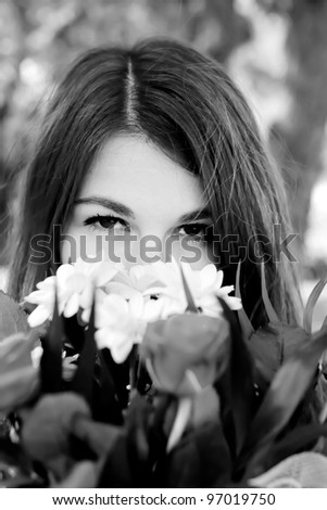 Black and white portrait of a beautiful young woman with flowers.