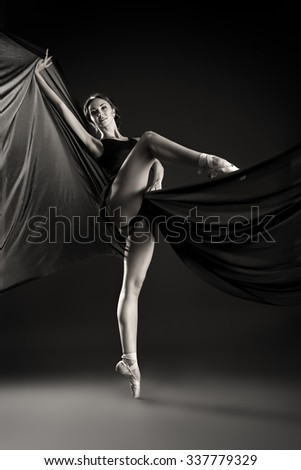 Black-and-white portrait of a graceful beautiful ballet dancer posing at studio. Art concept.