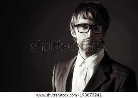 Black-and-white portrait of a handsome man in elegant black suit and spectacles. Over dark background. - stock photo