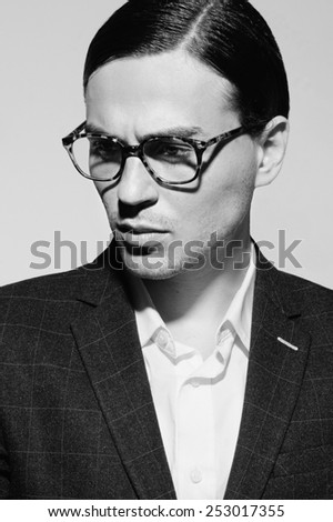 Black and white portrait of a handsome man with glasses and a suit in the studio on a white background, the concept of fashion, closeup - stock photo