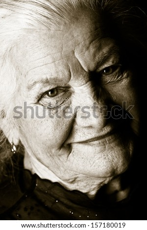 Black-and-white portrait of a happy senior woman smiling at the camera. Over black background. - stock photo