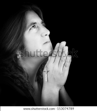 Black and white portrait of a latin woman praying and looking up (isolated on black with copy space)