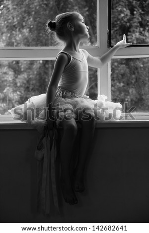 Black and white portrait of a little ballerina in pointes shoes is sitting on a Windowsill - stock photo
