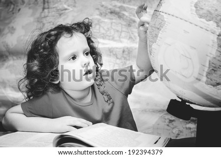 Black and white portrait of a little girl looks at the globe. - stock photo