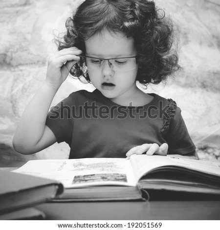 Black and white portrait of a  little girl with glasses reading a book, square image - stock photo