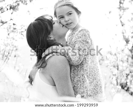 Black and white portrait of a mother and daughter relaxing together in a beautiful field, hugging and enjoying a sunny holiday outdoors. Family love and holiday activities lifestyle. - stock photo