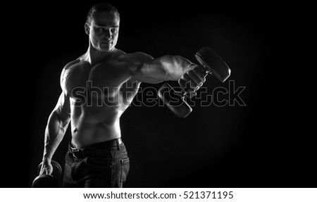 black-and-white portrait of a naked torso brutal male bodybuilder athlete pushes dumbbell on a black background