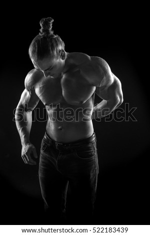 black-and-white portrait of a naked torso male bodybuilder athlete with a towel in the studio on a black background