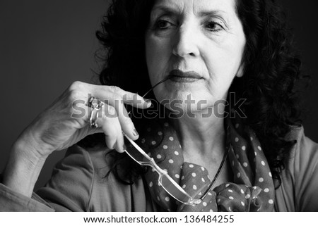 Black and White Portrait of a Pretty Older Woman with Reading Glasses - stock photo
