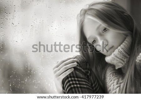 Black And White  Portrait of a sad Teenager Girl with long blonde Hair. She is sitting on a Window in the Rainy Autumn Day.