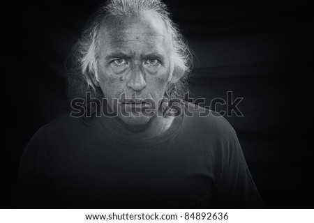 Black and white portrait of a scary looking man staring directly at viewer. - stock photo