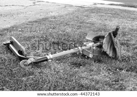 Black and white portrait of a scooter with an attached baseball glove and hat, and lunch box, laying on a lawn.