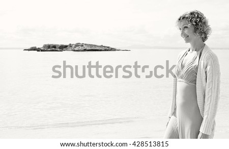 Black and white portrait of a senior beautiful healthy woman relaxinng on a sandy beach shore, smiling on summer holiday, nature outdoors. Travel lifestyle and healthy living, sunny exterior. - stock photo