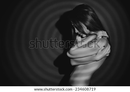Black-and-white portrait of a sensual naked woman posing over black background. Play of light and shadows.