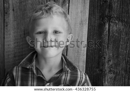 Black and white portrait of a seven year old boy with a barn wood background. - stock photo