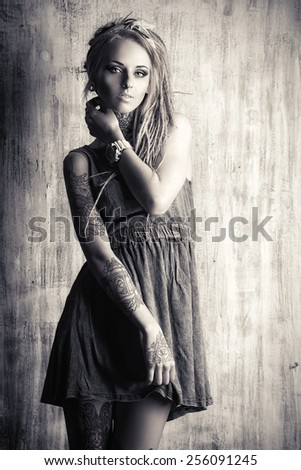 Black-and-white portrait of a sexual girl with fascinating dreadlocks posing by the grunge wall. Pin-up style.