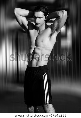 Black and white portrait of a sexy male fitness model outdoors - stock photo