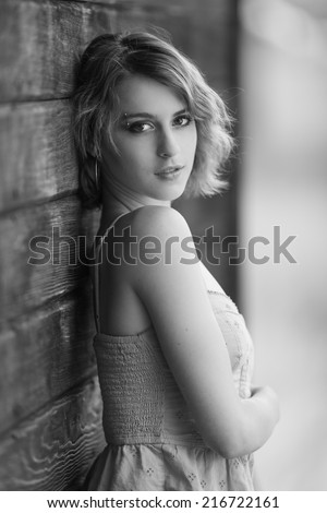 Black and white portrait of a short hair young model posing next to a wooden wall - stock photo