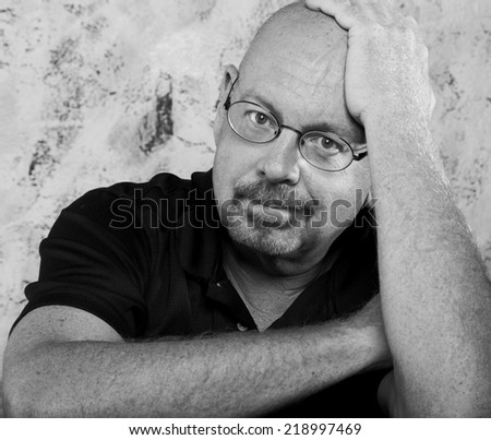 Black and White portrait of a smiling and confident mature balding senior man with  arms crossed, in front of a textured wall. - stock photo