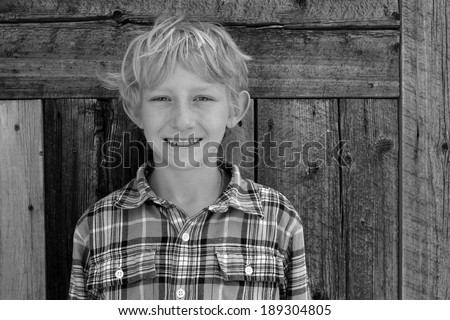 Black and white portrait of a smiling blond boy. - stock photo