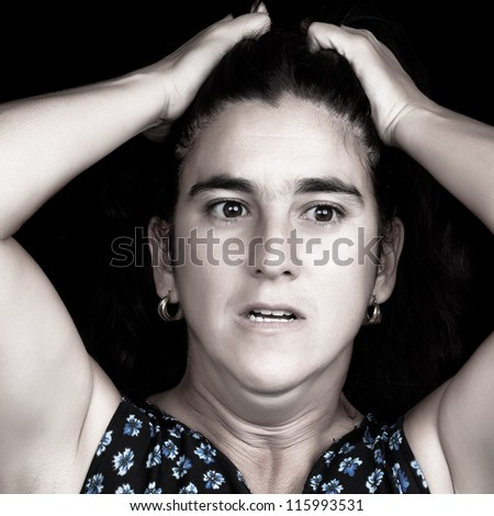 Black and white portrait of a stressed and depressed woman with her hands on her head and a very sad face isolated on black with space for text - stock photo