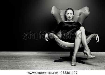 Black-and-white portrait of a stunning fashionable model sitting in a chair in Art Nouveau style. Business, elegant businesswoman. Interior, furniture. - stock photo