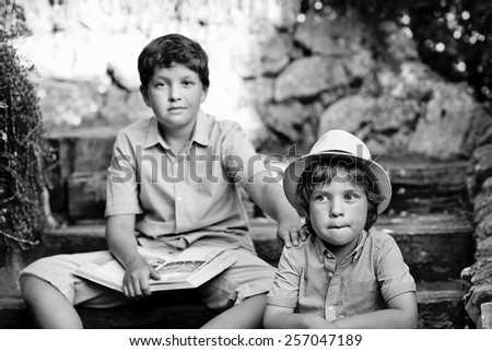 black and white portrait of a two brothers sitting on the stairs outdoors . - stock photo