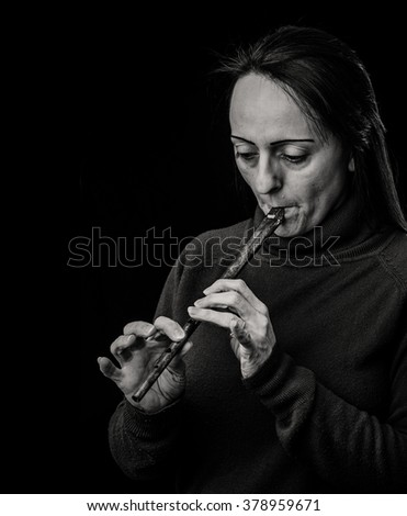 Black and White portrait of a woman playing a Tin Whistle against black background with copy space. - stock photo
