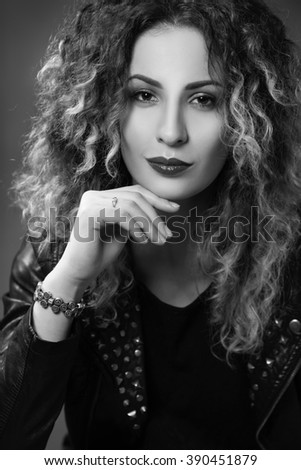 black-and-white portrait of a woman with curly hair and an enigmatic smile in the style of glam rock - stock photo