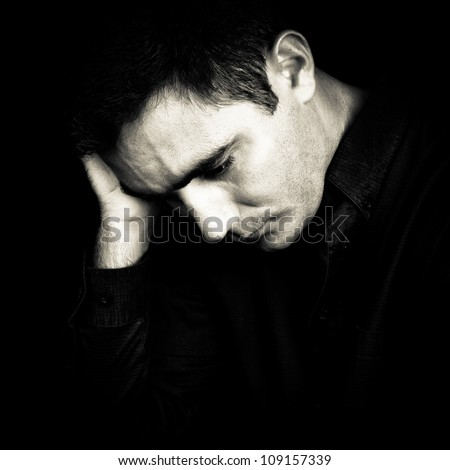 Black and white portrait of a worried and depressed man isolated on black - stock photo