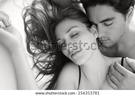 Black and white portrait of a young attractive romantic couple kissing, laying down on a white bed, having sex and being loving with each other. Love and relationships lifestyle, interior bedroom. - stock photo