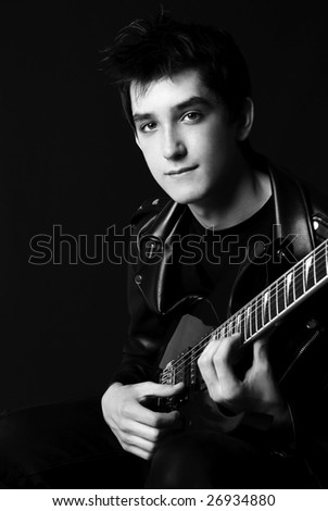 black and white portrait of a young handsome man playing guitar