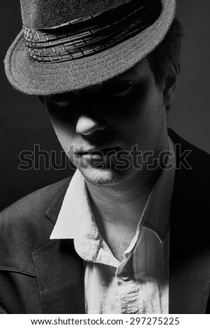 Black and white portrait of a young man in a hat and suit - stock photo