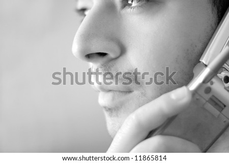 Black and white portrait of a young man on his cell phone.  He is listening with a  serious look of concern on his face. - stock photo