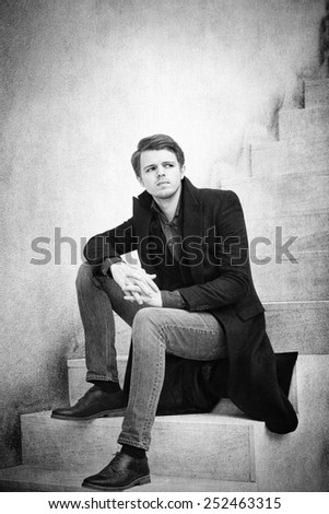 Black and white portrait  of a young sad man sitting on the stairs. - stock photo