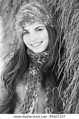 Black and white portrait of a young woman outdoor by a hay stack. - stock photo