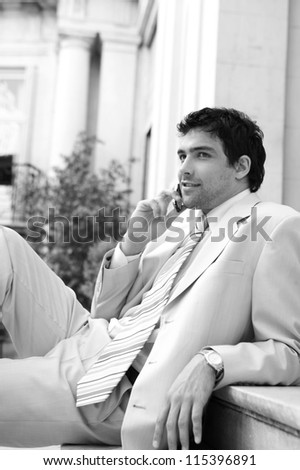 Black and white portrait of an attractive businessman having a conversation on his cell phone while sitting on a classic office building's steps.