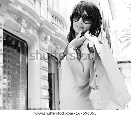 Black and white portrait of an attractive consumer woman walking on a shopping street with elegant buildings and stores, carrying paper bags during a fun and sunny day, turning to smile at camera. - stock photo