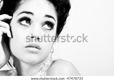 Black-and-white portrait of an attractive young woman with fancy accessories looking away longingly. Horizontal shot. Isolated on grey.