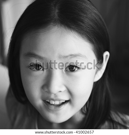 black and white portrait of an eight-year old asian girl smiling. - stock photo