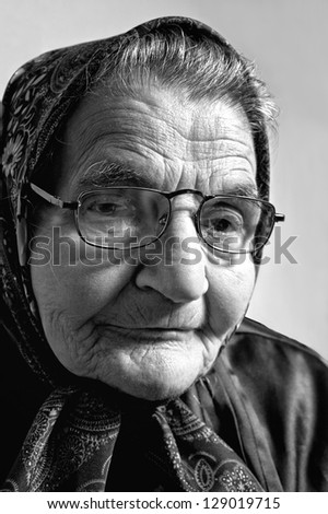 Black and white portrait of an elderly woman. Dreaming the past. - stock photo