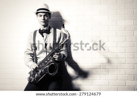 Black-and-white portrait of an elegant musician standing with his saxophone by the brick wall. Art and music. Jazz music. - stock photo