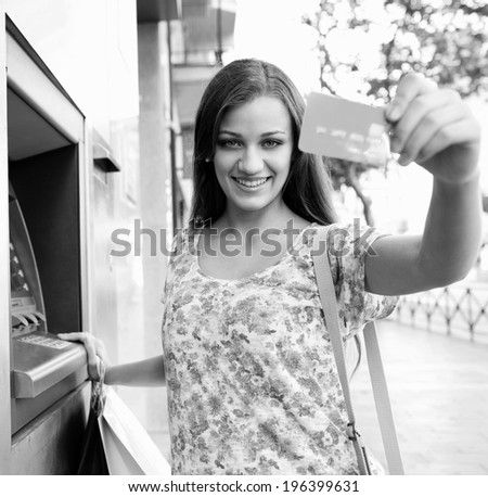Black and white portrait of attractive woman using a cash machine point to withdraw money, and showing off her credit card joyfully, carrying shopping bags during a sunny day in the city, lifestyle. - stock photo