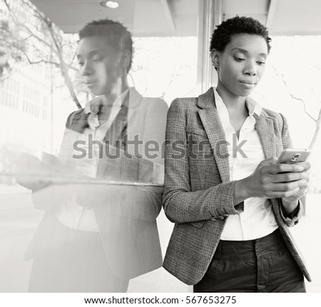 Black and white portrait of beautiful african american business woman, office building mirror reflections in financial city, using smart phone outdoors. Professional black woman technology lifestyle.